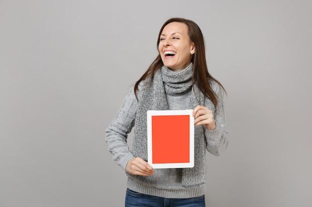 灰色のセーターのスカーフで笑っている女性は、灰色の背景に分離された空白の空の画面でタブレットpcコンピューターを保持します。寒い季節のコンセプトをコンサルティングする健康的なライフスタイルのオンライン治療。コピースペースをモックアップします。