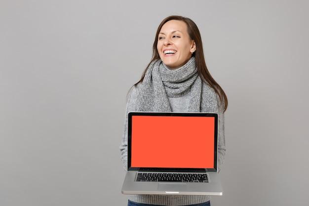 灰色のセーターを着て笑っている女性、脇を向いているスカーフ、灰色の背景で隔離の空白の空の画面でラップトップpcコンピューターを保持します。健康的なライフスタイル、オンライン治療コンサルティング、寒い季節のコンセプト。