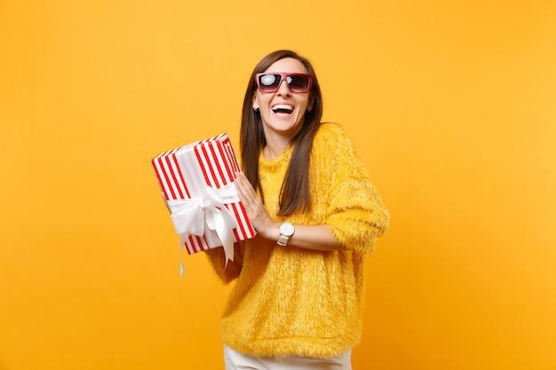 明るい黄色の背景で隔離の休日を楽しんで、祝うギフトプレゼントと赤い箱を保持している赤い眼鏡で笑う女性。人々の誠実な感情、ライフスタイルのコンセプト。広告エリア。