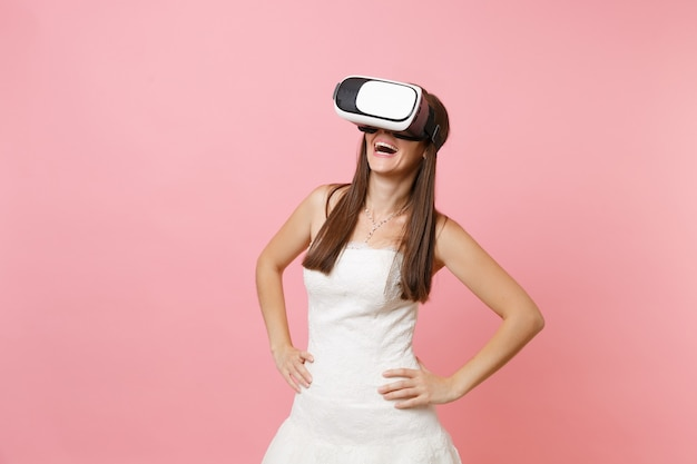 白いドレスを着て笑う女性と腕を腰に当てて立っているバーチャルリアリティのヘッドセット