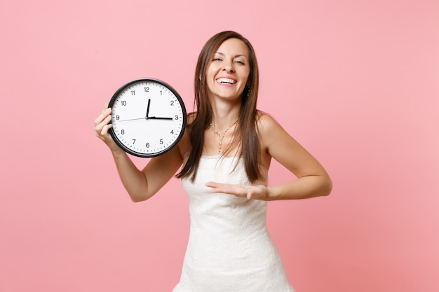 Смеющаяся женщина в белом платье, указывая рукой на будильник