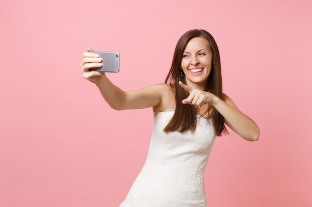 携帯電話で自分撮りショットを撮って、ビデオ通話をしているカメラに人差し指を指している白いドレスを着て笑っている女性