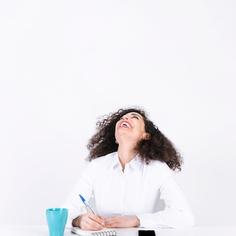 Laughing woman making notes