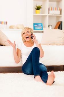 居間で電話で笑う女性