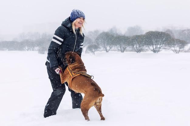 笑う女性はウィンターパークでボクサー犬と遊ぶ。愛と友情。
