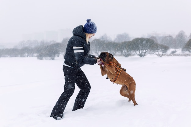 Laughing woman plays with boxer dog in winter park. love and friendship.