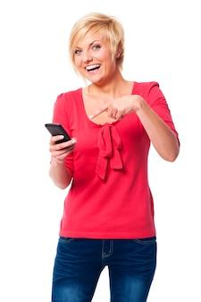 Donna di risata che indica sul telefono cellulare