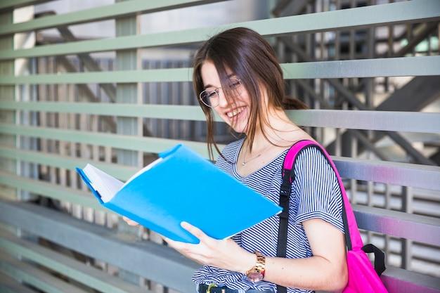 Libro di lettura di risata della donna vicino alla parete