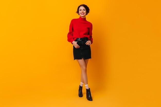 Donna che ride in minigonna in piedi con le mani in tasca