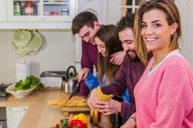 Смеется женщина, улыбаясь в камеру, говорить и готовить еду за столом с друзьями, полными овощей и макарон