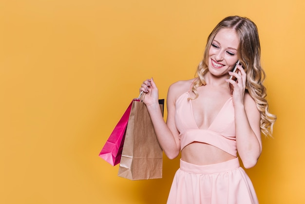 Laughing woman speaking on phone while shopping