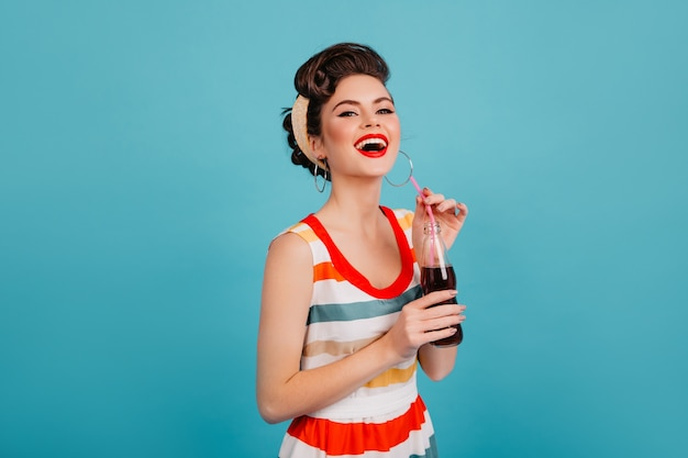 Laughing woman in striped dress drinking soda. studio shot of happy pinup girl with beverage isolated on blue background.