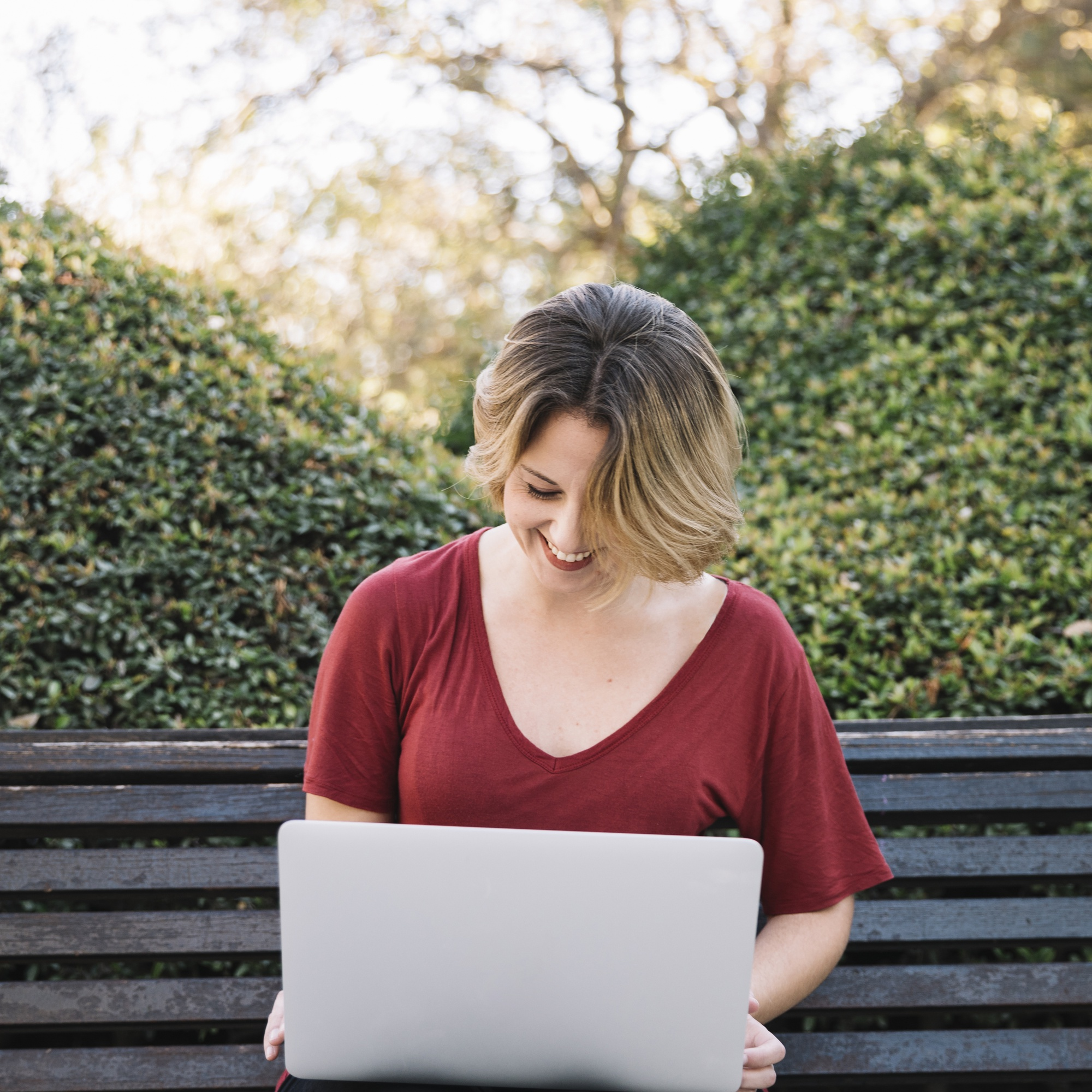 Laughing woman using laptop in park