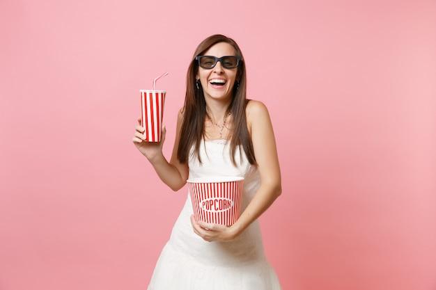 Ridendo donna in abito bianco occhiali 3d guardando film tenendo secchio di popcorn, bicchiere di plastica di soda o cola
