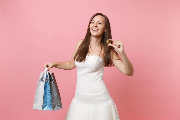 Laughing woman in white dress hold bitcoin metal coin of golden color multi colored packages bag with purchases after shopping