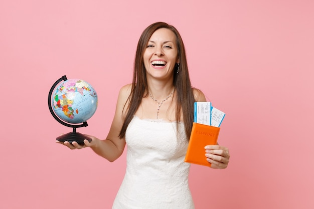 Laughing woman in white dress holding world globe, passport boarding pass ticket going abroad, vacation
