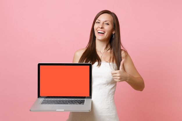 Laughing woman in white dress showing thumb up, hold laptop pc computer with blank black empty screen
