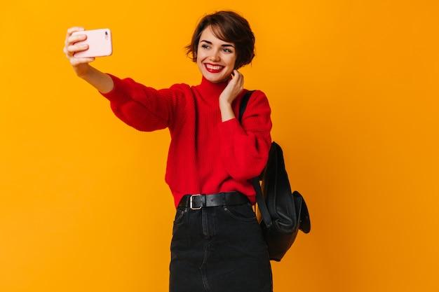 黄色の壁にポーズをとってバックパックと笑う女性