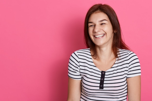 Laughing woman with dark hair posing isolated over rosy wall, happy girl wearing striped t shirt, expressing happiness and joy. copy space for advertisement.