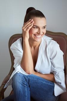 肘掛け椅子に座って目を閉じて笑っている女性。スタジオショット