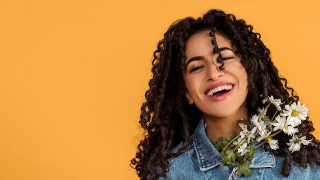 花を持つ女性を笑ってください。