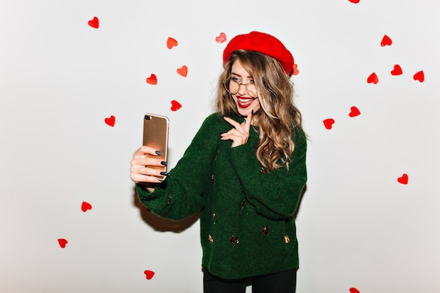 Laughing woman with gorgeous hairstyle making selfie with hearts on wall