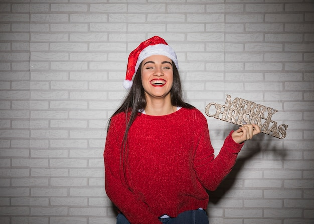 Laughing woman with merry christmas sign