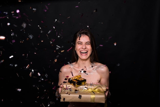 Laughing woman with present boxes between confetti