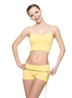 測定タイプ-白で隔離と腰を測定するセクシーなスリムなボディを持つ女性を笑ってください。