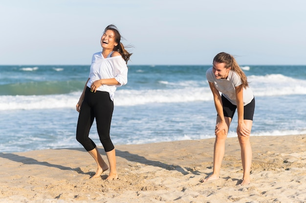 Laughing women on the beach while jogging