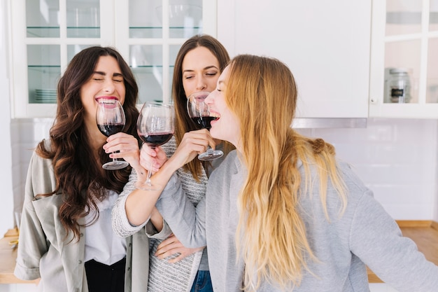 Laughing women drinking wine