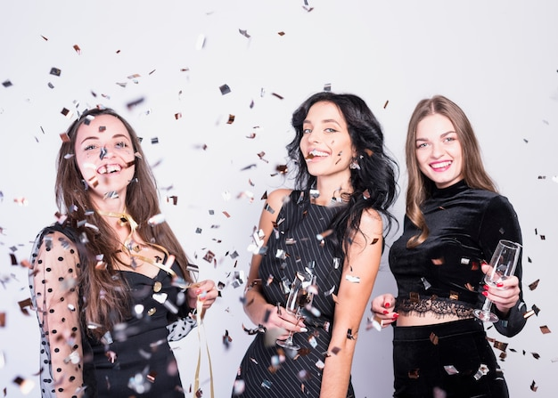 Laughing women in eveningcloths with glassesbetween throwing confetti