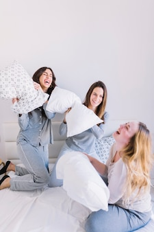 Laughing women fighting with pillows
