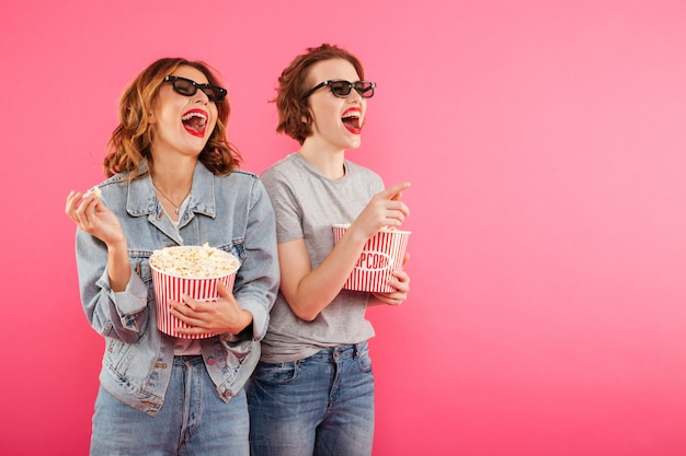 Laughing women friends eating popcorn watch film.