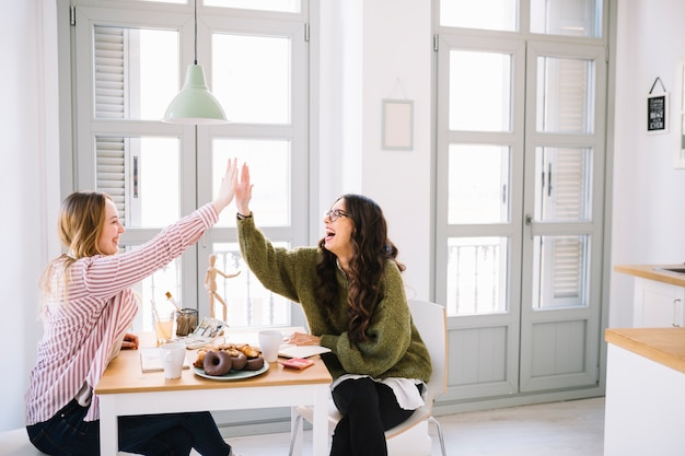 Laughing women high-fiving over table