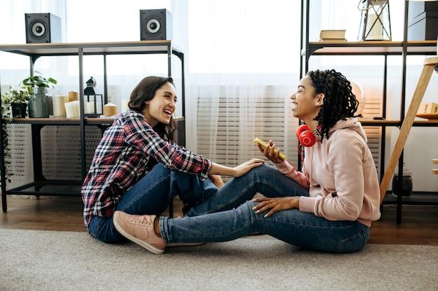 ヘッドフォンで笑う女性は、家で音楽を楽しんでいます。イヤホンをしたかわいいガールフレンドが部屋でくつろぎ、音の愛好家がソファで休んで、女性の友達が一緒にレジャーをする