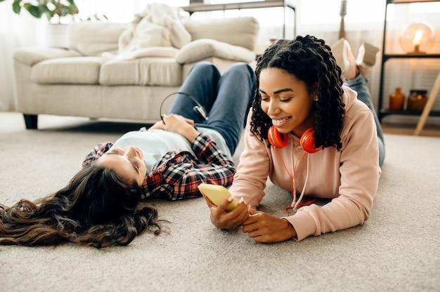 家では床に寝転がって音楽を聴きながら、ヘッドフォンを付けて笑う女性たち。イヤホンをしたかわいいガールフレンドが部屋でくつろぎ、音の愛好家がソファで休んで、女性の友達が一緒にレジャーをする