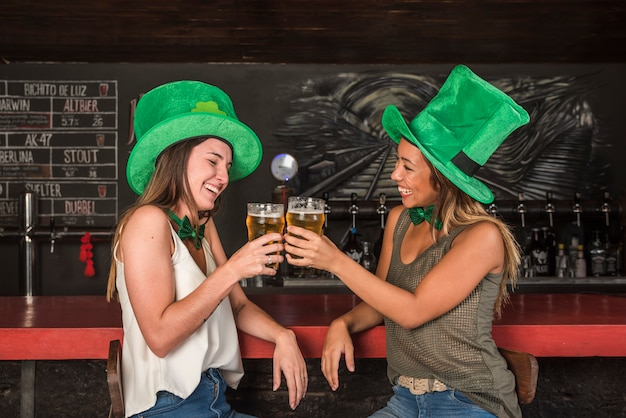 Laughing women in saint patricks hats clanging glasses of drink at bar counter