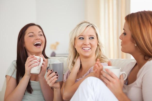 カップでソファーに座っている女性を笑う