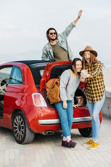 Laughing women taking selfie on smartphone near car trunk and man leaning out from auto