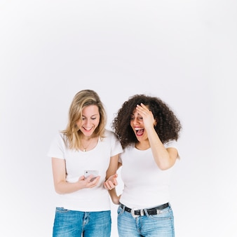 Laughing women using smartphone together