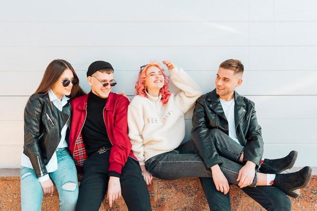 Смеются молодые и привлекательные друзья, сидя на скамейке