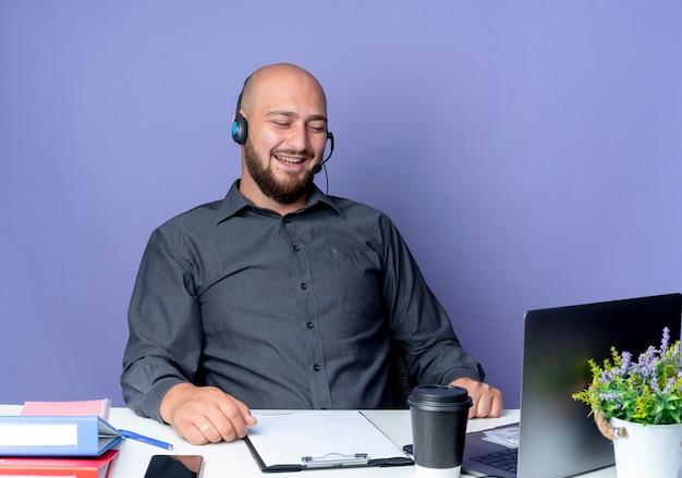 Ridendo giovane calvo call center uomo che indossa auricolare seduto alla scrivania con strumenti di lavoro guardando laptop isolato su sfondo viola