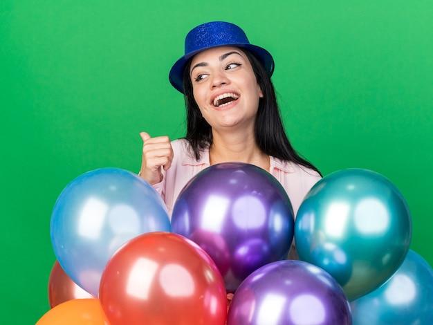 緑の壁に分離された親指を示す風船の後ろに立っているパーティーハットを身に着けている若い美しい女性を笑う