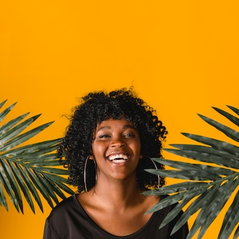 Laughing young black woman with palm leaves on colored background