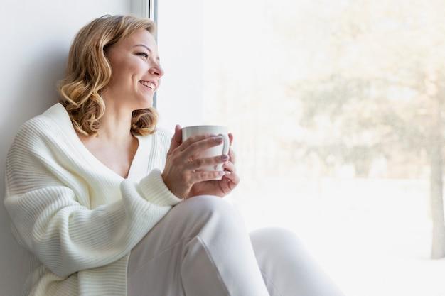 居心地の良い家庭服を着て笑っている若いブロンドの女性は、カップと窓のそばに座っています。コロナウイルスのパンデミック時の検疫と自己隔離。