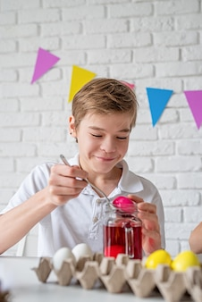 Laughing young boy coloring eggs for easter at home