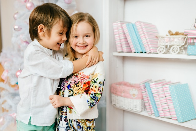 Laughing young boy hugging his pretty girlfriend in brigh room with cristmas tree.