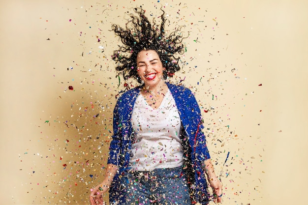 Laughing young brunette girl sprinkled with confetti. festive mood. new year's and christmas. yellow wall.