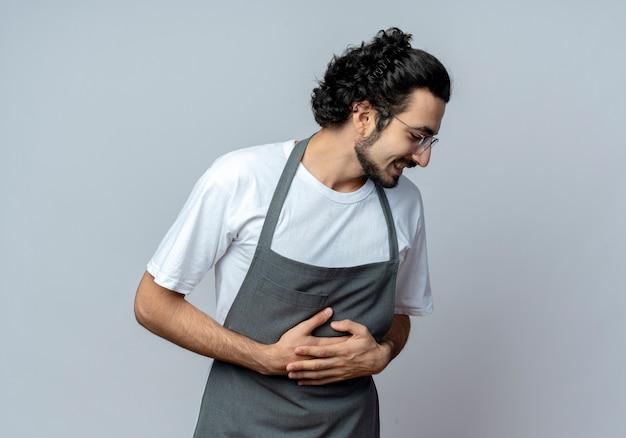Смеющийся молодой кавказский парикмахер в очках и с волнистой лентой для волос в униформе, положив руки на живот, глядя вниз, изолированные на белом фоне с копией пространства